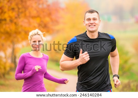 cheerful young athletes jogging autumn morning - stock photo