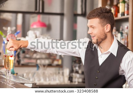 Cheerful young bartender is making cocktails in bar. He is standing at counter and smiling. The man is pouring red substance into glasses with inspiration - stock photo