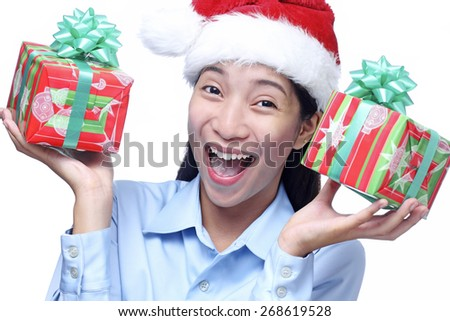 Cheerful young beautiful asian lady holding a christmas gifts. Isolated in white background. - stock photo