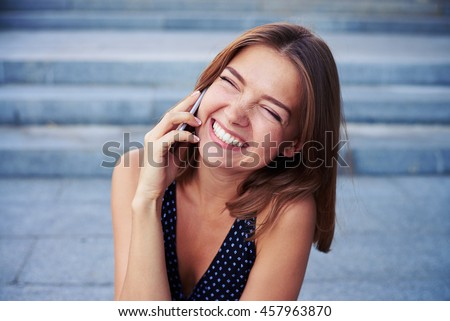 Cheerful young beautiful woman is laughing with eyes closed while talking on the phone on the street - stock photo