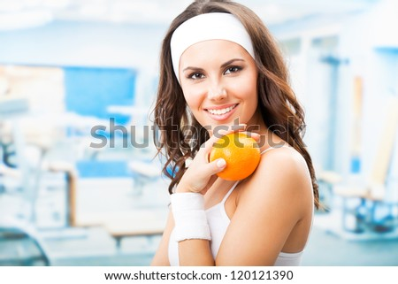 Cheerful young beautiful woman with orange, at fitness center or gym - stock photo