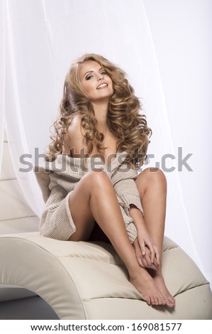 Cheerful young beauty sitting on the couch in bright room and smiling, relaxing