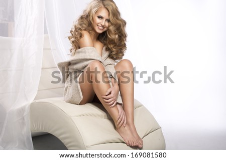 Cheerful young beauty sitting on the couch in bright room and smiling, relaxing - stock photo