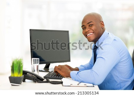 cheerful young black businessman using computer in office - stock photo