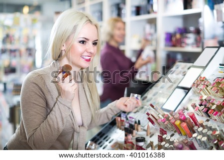 Cheerful young blonde woman choosing face powder on display and smiling - stock photo