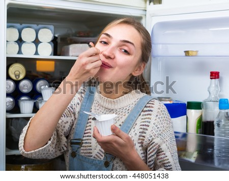 Cheerful young blonde woman eating sour cream near opened refrigerator at kitchen  - stock photo