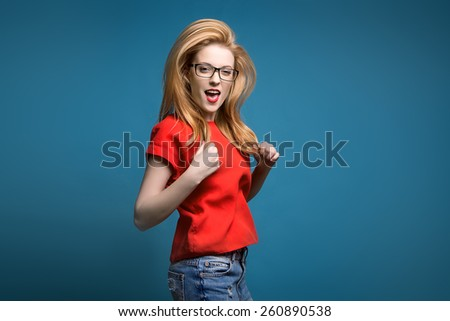 cheerful young blonde woman jumping. studio, blue background. fun, joy, movement - stock photo
