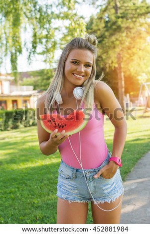 Cheerful young blonde woman with headphones, eating watermelon in park on sunny summer day. Cute happy teenage girl eating fresh fruit. Vibrant colors. - stock photo