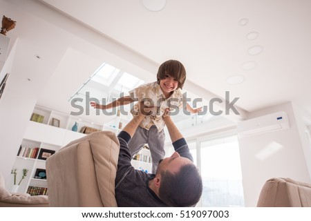Cheerful young boy having fun with father on sofa