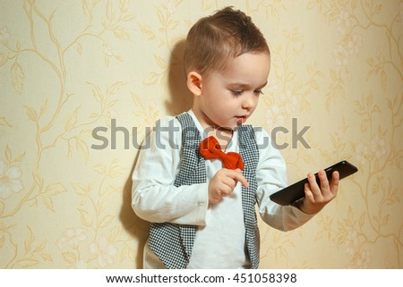 cheerful young boy in elegant suit with red bowtie playing with mobile phone - stock photo