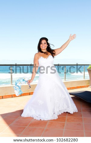 cheerful young bride on balcony - stock photo