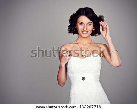 cheerful young bride over grey background - stock photo