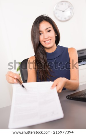 cheerful young brunette business woman holding a pen to customer and inviting to sign a contract - stock photo