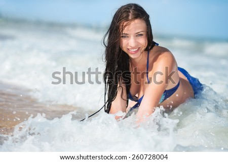 Cheerful young brunette posing in the water - stock photo