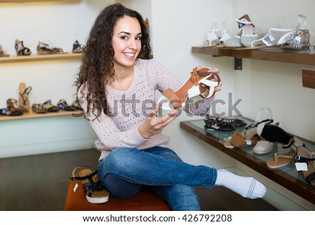 Cheerful young brunette trying on fashion summer shoes in a shoe store - stock photo