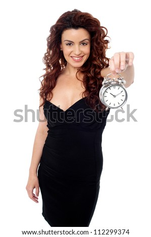 Cheerful young brunette wearing a black dress holding a timepiece in her stretched left arm and posing - stock photo