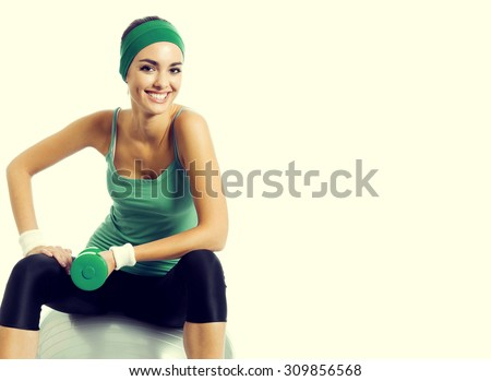Cheerful young brunette woman in green fitness wear exercising with dumbbell and fitball, with blank copyspace area for slogan or text - stock photo
