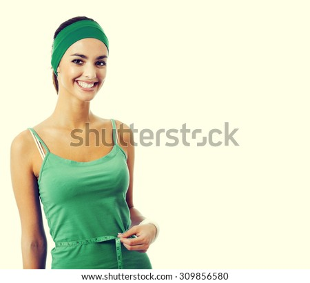 Cheerful young brunette woman in green fitness wear measuring waist with a tape measure, with blank copyspace area for slogan or text - stock photo