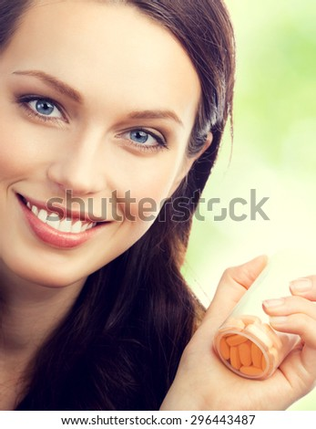 Cheerful young brunette woman showing bottle with pills, outdoor