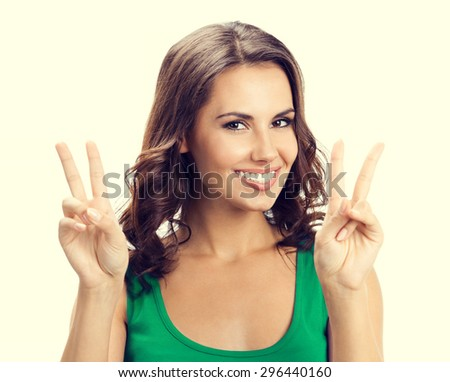 Cheerful young brunette woman showing two fingers or victory gesture, in smart green casual clothing - stock photo