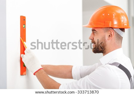 Cheerful young builder is measuring wall of building. He is holding a ruler and drawing the line. The man is standing and smiling - stock photo