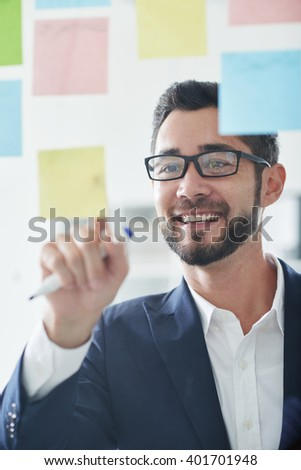 Cheerful young business executive writing his ideas on stick notes - stock photo