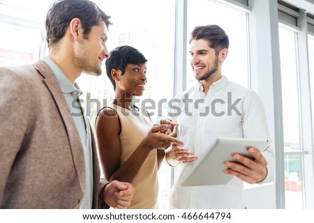 Cheerful young business people talking and using tablet together in office