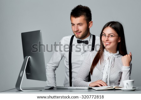 Cheerful young business people working with computer  isolated on grey background. - stock photo