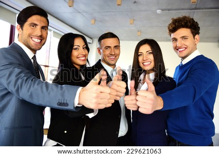 Cheerful young business team with thumbs up sign