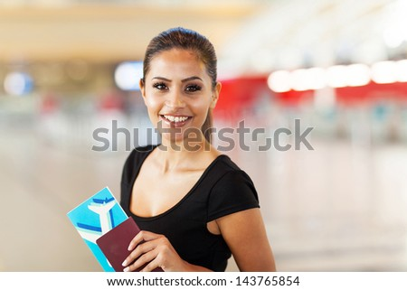 cheerful young business woman with passport and air ticket in airport - stock photo