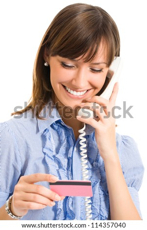 Cheerful young business woman with plastic card and phone, isolated over white background - stock photo