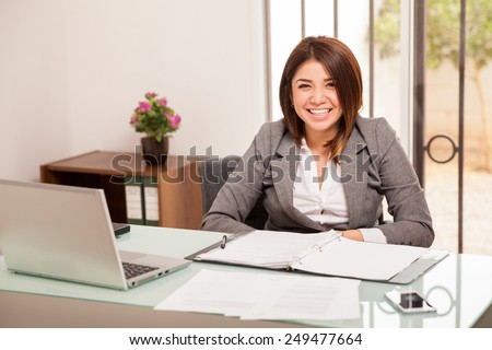 Cheerful young business woman working at her office and smiling - stock photo