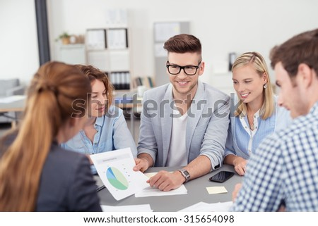 Cheerful Young Businessman Explaining a Business Chart on a Paper to Colleagues Inside the Boardroom. - stock photo