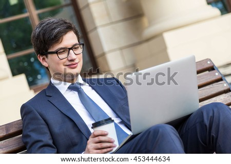 Cheerful young businessman in suit sitting on wooden bench with coffee cup in hand and laptop placed on his lap. Side view - stock photo