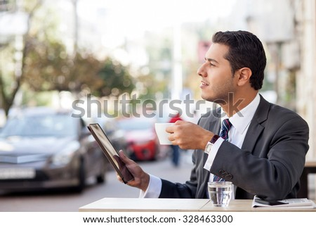 Cheerful young businessman is using tablet in cafeteria. He is sitting outdoors and drinking coffee. The worker is looking forward dreamingly and smiling - stock photo