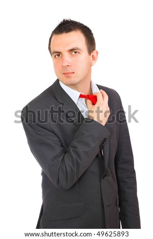 Cheerful young businessman mend a tie. Isolated