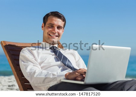 Cheerful young businessman on the beach lying on a deck chair with his computer - stock photo