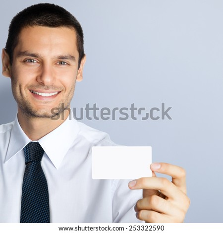 Cheerful young businessman showing blank business or plastic credit card, with copyspace area for text or slogan, against grey background - stock photo