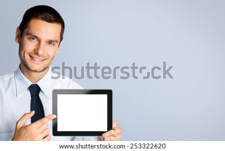 Cheerful young businessman showing blank no-name tablet pc monitor, against grey background, with copyspace area - stock photo