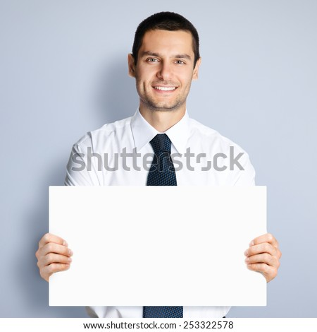 Cheerful young businessman showing blank signboard, against grey background - stock photo