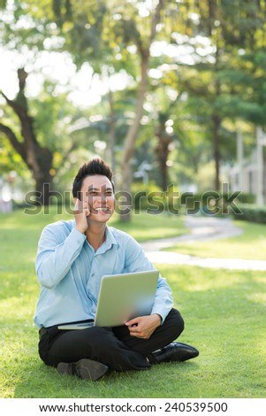 Cheerful young businessman sitting in the park with laptop and talking on the phone