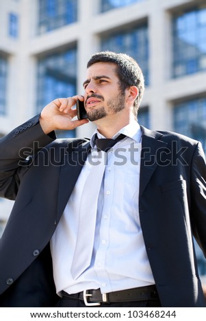 Cheerful young businessman using mobile phone