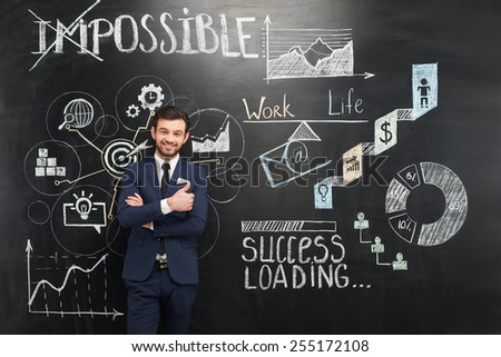 Cheerful young businessman with thumb up standing on dark chalkboard background. Colorful symbols and graphs painted on it. Concept for successful project