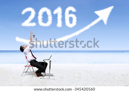 Cheerful young businessman working with laptop on the beach under clouds shaped numbers 2016 and upward arrow - stock photo