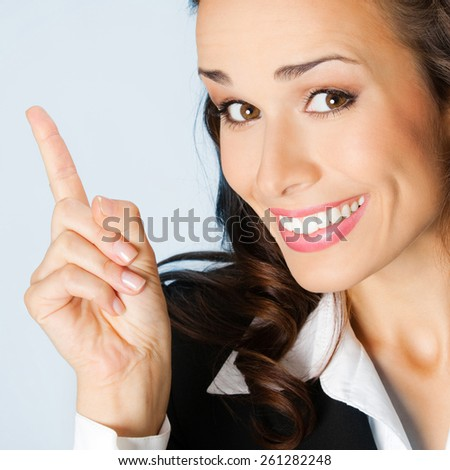Cheerful young businesswoman showing blank area for sign or copyspase, against blue background - stock photo