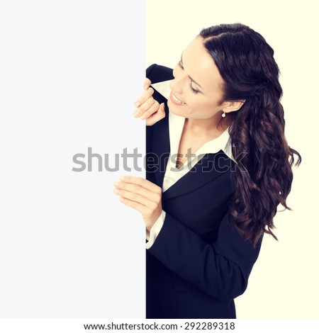 Cheerful young businesswoman showing blank signboard - stock photo