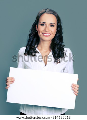 Cheerful young businesswoman showing blank signboard with blank copyspace area for text or slogan - stock photo