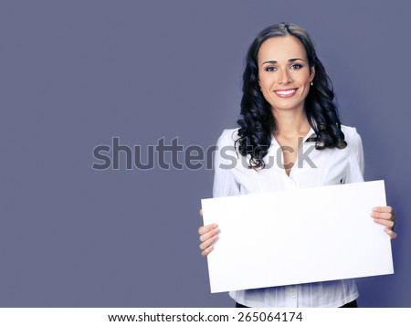 Cheerful young businesswoman showing blank signboard with copyspace area for text or slogan, over violet background - stock photo