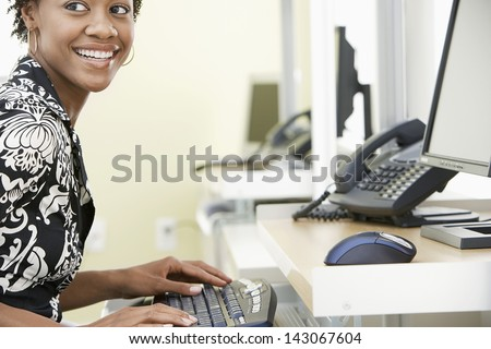 Cheerful young businesswoman typing on computer keyboard in office - stock photo
