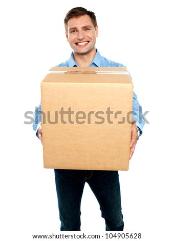 Cheerful young casual guy carrying packed cardboard boxes isolated on white background